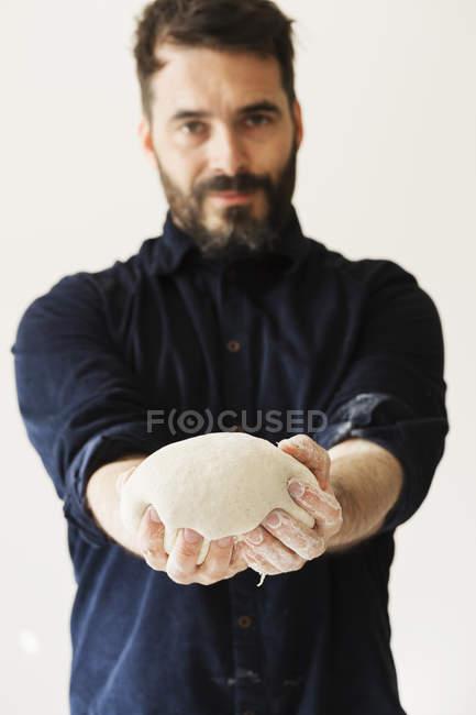 Пекарь держит часть хлебного теста — стоковое фото