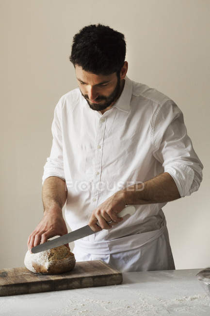 Baker slicing a loaf of bread — Stock Photo