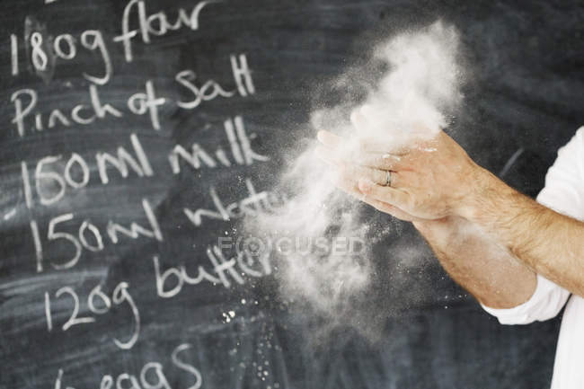 Baker dusting his hands with flour. — Stock Photo