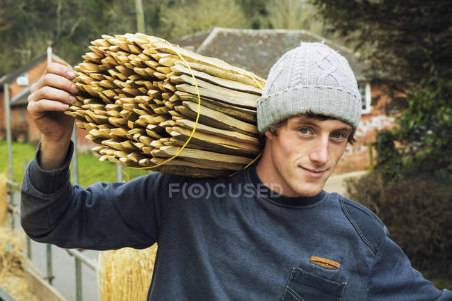 Thatcher carrying bundle of wooden pegs — Stock Photo