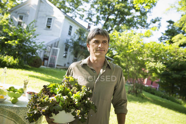 Man carrying large bowl of lettuce — Stock Photo