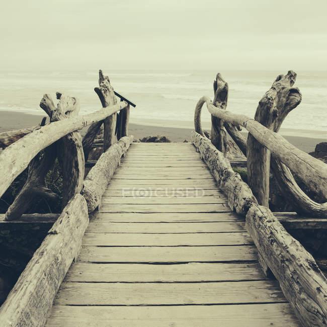 Pont en bois flotté face à l'océan Pacifique — Photo de stock
