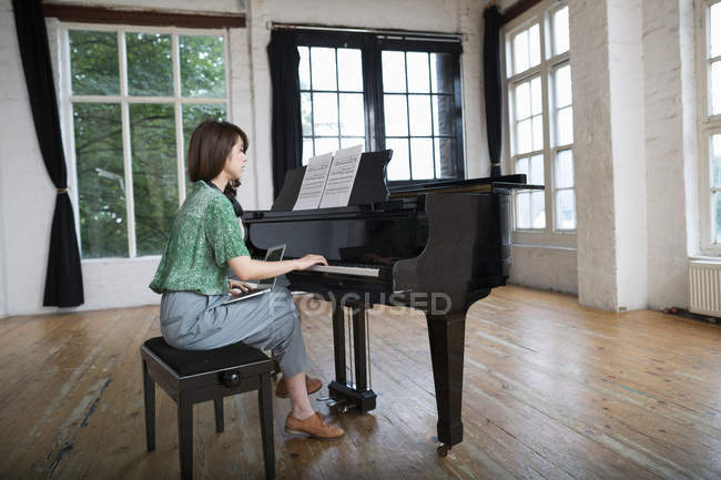 Woman playing on a grand piano — Stock Photo