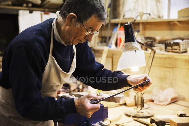 Mann arbeitet an einem Stück Holz — Stockfoto