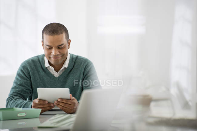 Man sitting holding digital tablet — Stock Photo