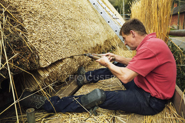 Thatcher trimming straw — Stock Photo
