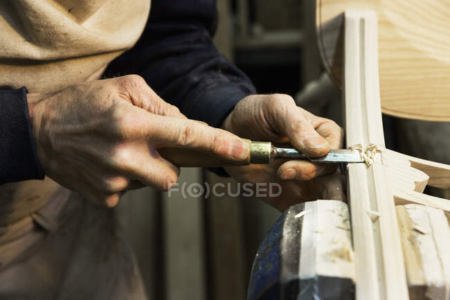 Man working on a wooden chair with a chisel. — Stock Photo