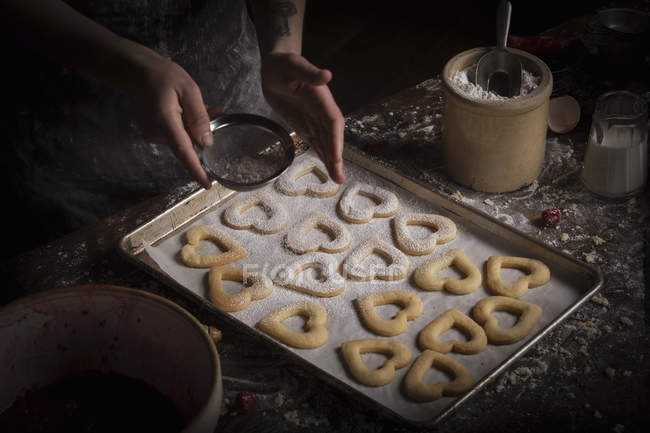 Woman sprinkling icing sugar over biscuits — Stock Photo