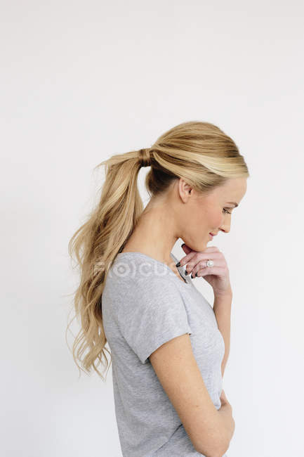 Blonde woman with one hand on chin — Stock Photo