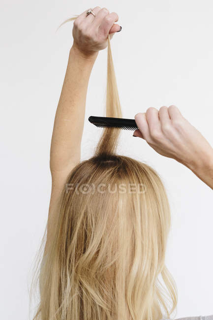 Woman with blond hair using comb — Stock Photo