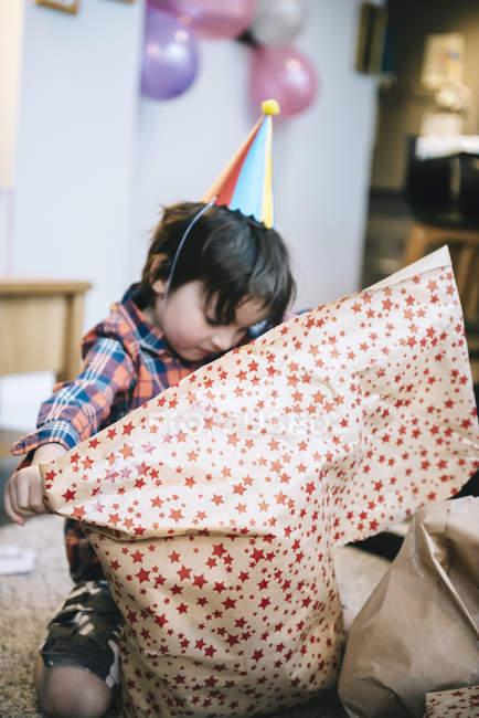 Хлопчик, розгортаючи свої подарунки — стокове фото