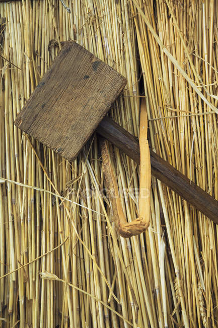 Wooden mallet and peg on straw — Stock Photo
