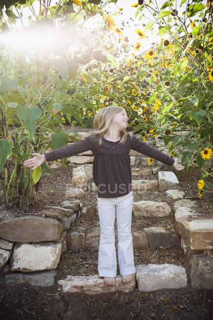 Ребенок, стоящий на садовой дорожке — стоковое фото