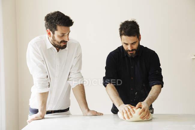 Bakers kneading bread dough. — Stock Photo