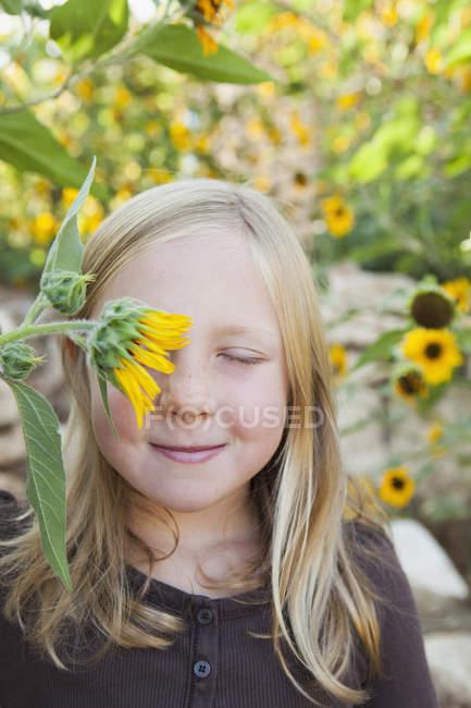 Menina com flor sol na frente do olho — Fotografia de Stock