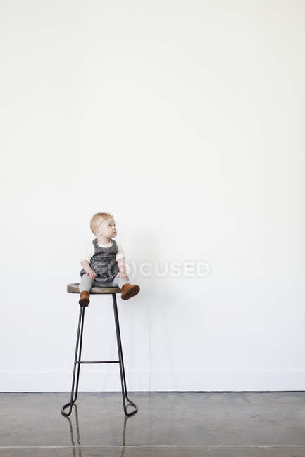 Girl sitting on tall stool — Stock Photo