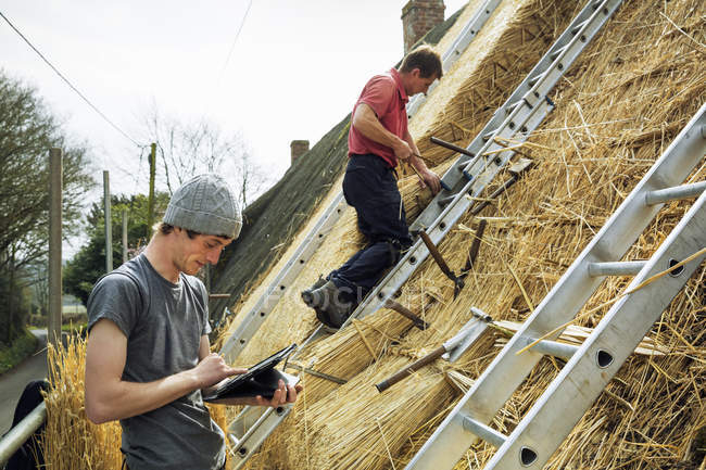 Thatchers thatching a roof — Stock Photo