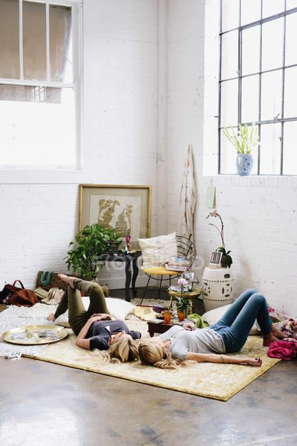 Frauen auf dem Boden liegend mit Kissen und persönlichem Besitz — Stockfoto