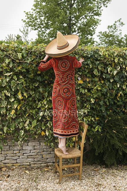 Женщина, стоя на стуле и смотрит через стену — стоковое фото