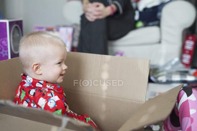 Rapaz sentado em uma caixa de papelão grande — Fotografia de Stock