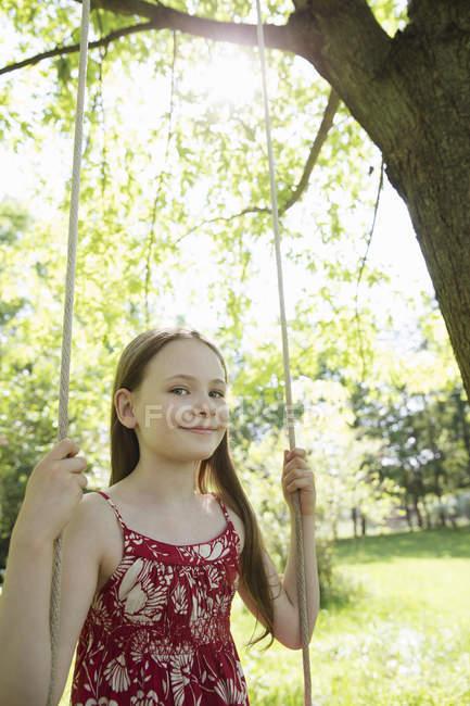 Girl in sundress on swing — Stock Photo