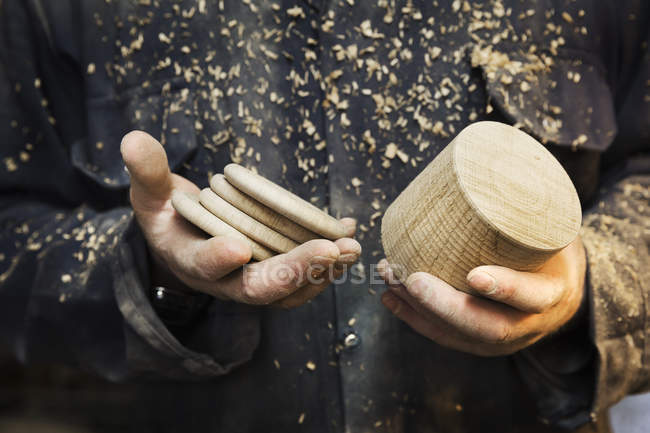 Man with wooden shape and wooden discs — Stock Photo