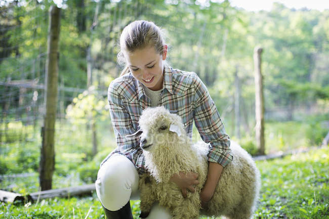 Teenager kniend und Arme um Ziege — Stockfoto