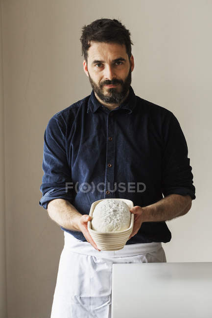 Baker holding a freshly baked loaf — Stock Photo