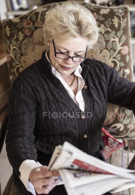 Frau auf Highback Sofa lesen Zeitung — Stockfoto