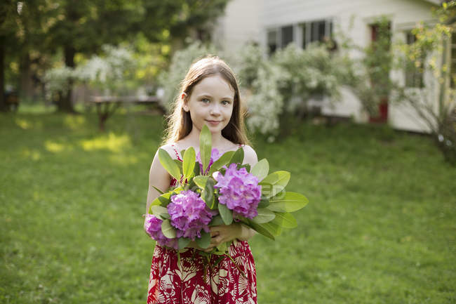 Girl holding bunch of flower heads — Stock Photo