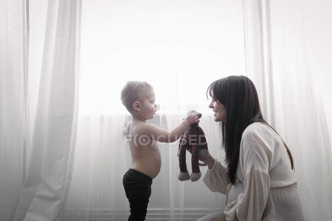 Pregnant woman playing with son — Stock Photo