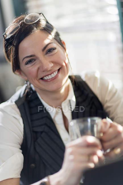 Frau Glas halten und Lächeln in die Kamera — Stockfoto