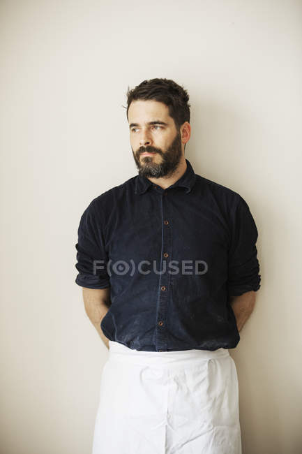 Male baker wearing a white apron. — Stock Photo