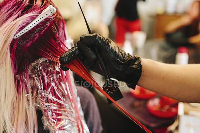 Colorista per capelli applicando il colore rosa — Foto stock