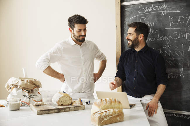 Bakers using a laptop computer — Stock Photo