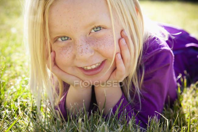 Jeune fille allongée sur l'herbe — Photo de stock