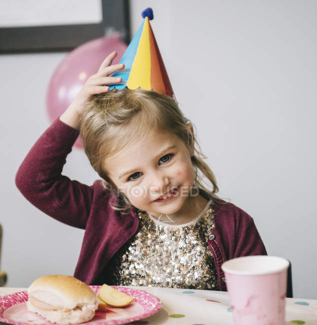 Girl in a party hat at a birthday party. — Stock Photo