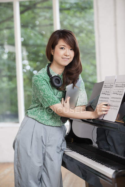 Woman standing next to a grand piano — Stock Photo