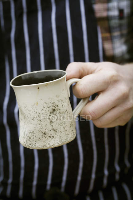 Chef holding a mug. — Stock Photo