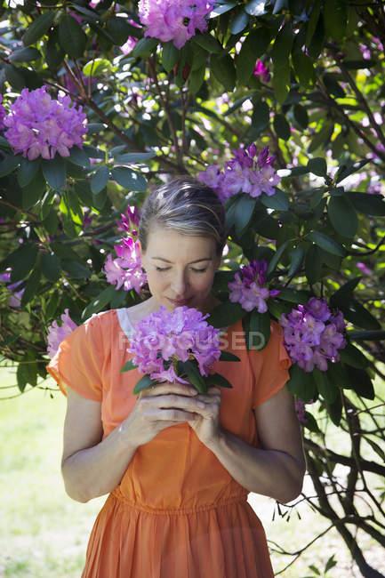 Mulher segurando cabeça flor roxa — Fotografia de Stock
