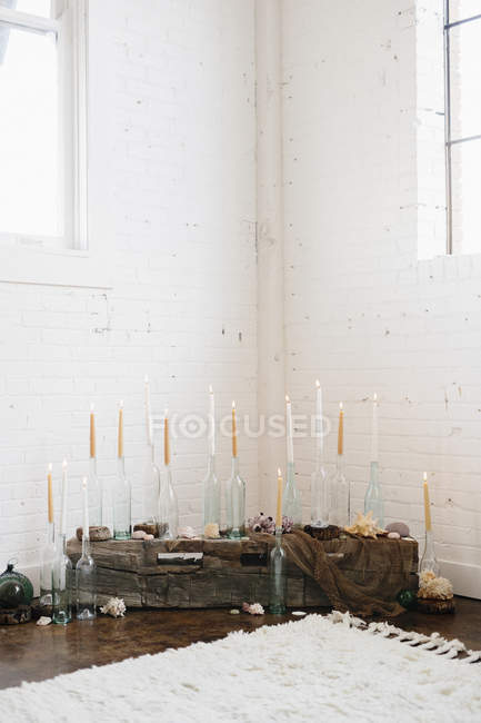 Candles in glass bottles arranged in corner — Stock Photo