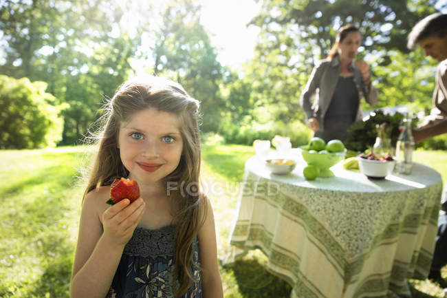 Girl holding a large fresh strawberry — Stock Photo