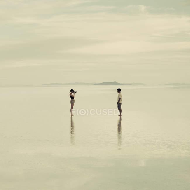 Pareja en Bonneville Salt Flats inundados - foto de stock