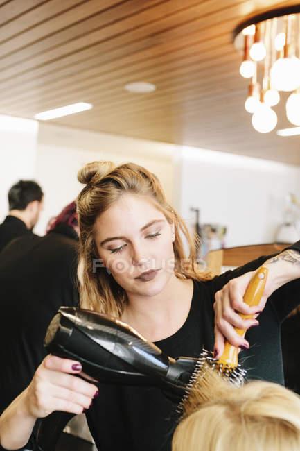 Hair stylist blowdrying hair. — Stock Photo