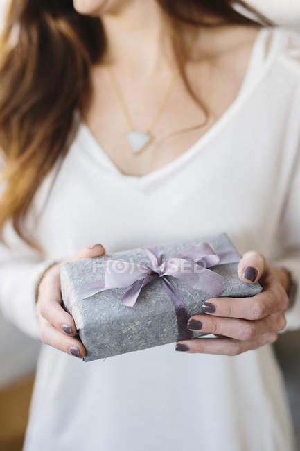 Woman holding package with large ribbon — Stock Photo