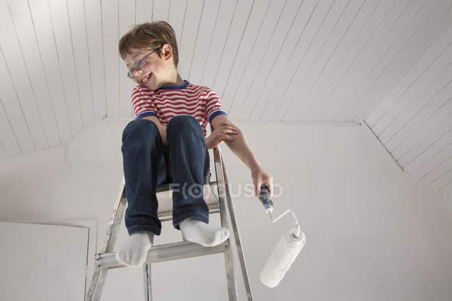 Junge sitzt auf Stehleiter mit Farbroller — Stockfoto