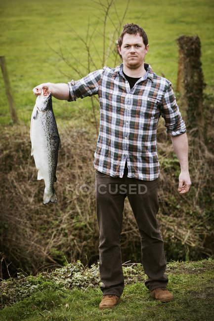Man holding a salmon fish. — Stock Photo