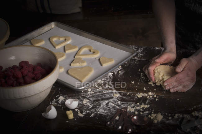 Woman baking heart shaped biscuits — Stock Photo