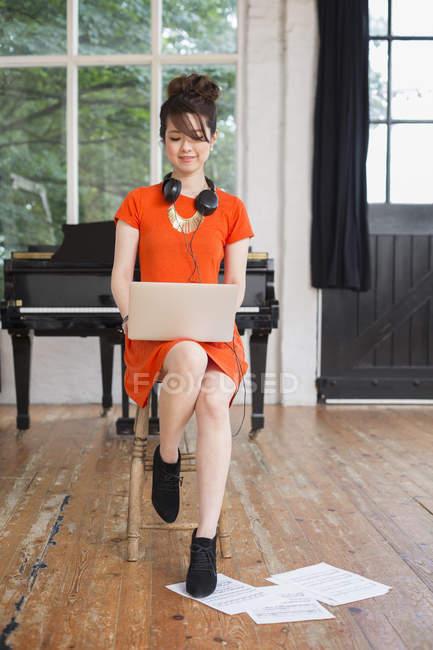Woman wearing headphones in rehearsal studio — Stock Photo