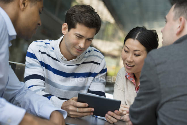 Four people gathered around digital tablet — Stock Photo